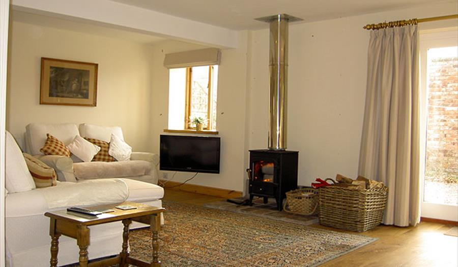 Cosy in the lounge with wood burner at Manor Farm Holiday Cottages - SC